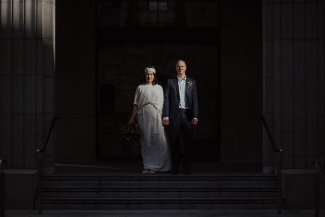 Bride and Groom standing in front of impressive building with sunlight falling on them, Wellington City Wedding, Ana Galloway Photography