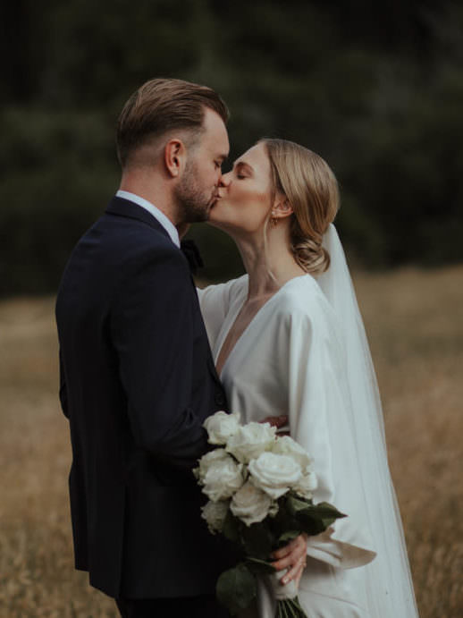 Intimate wedding bride and groom kissing and embracing in a field of summer grass, Groom wears a tuxedo and bride wears a Charlie Brear gown - Ana Galloway Photography