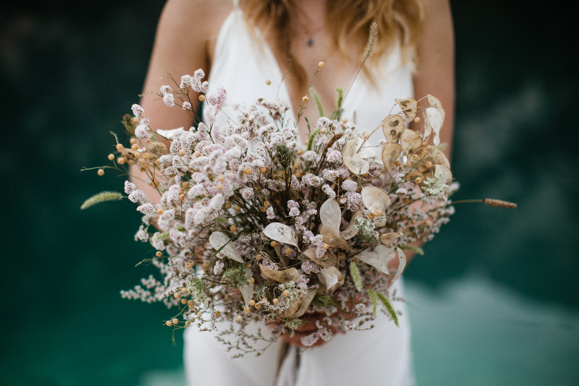 Bride holding dried bouquet at Lago di Braies in the Dolomites in Italy during elopement wedding Ana Galloway Photography