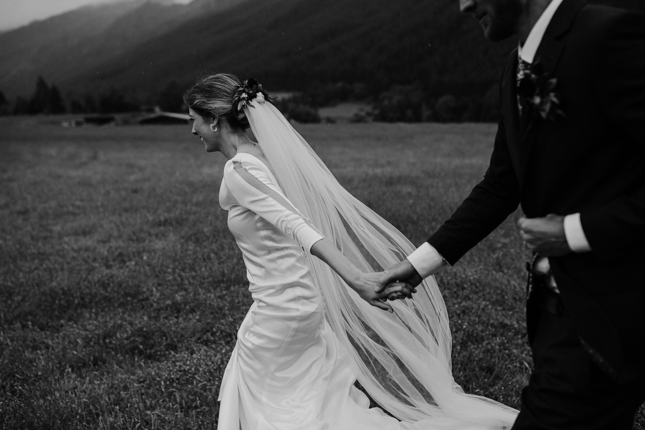Bride and Groom smiling and running in a field with the veil flying