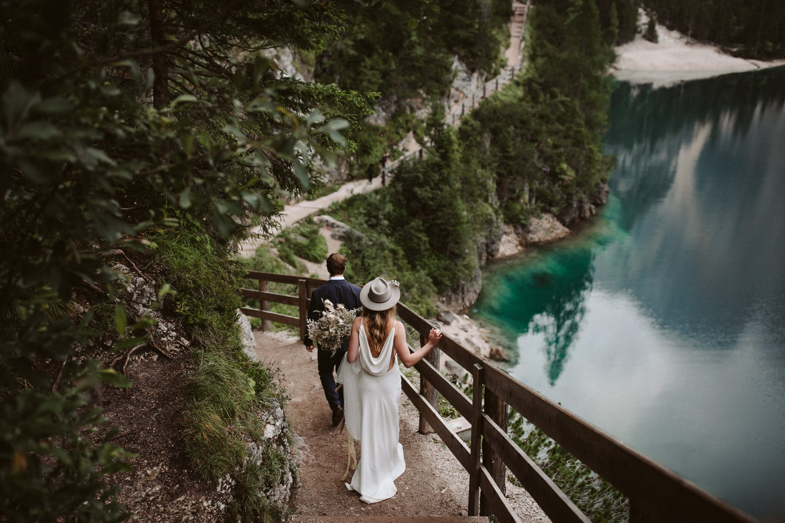 Bride and Groom walking along track at Lago di Braies in the Dolomites in Italy during their elopement wedding Ana Galloway Photography