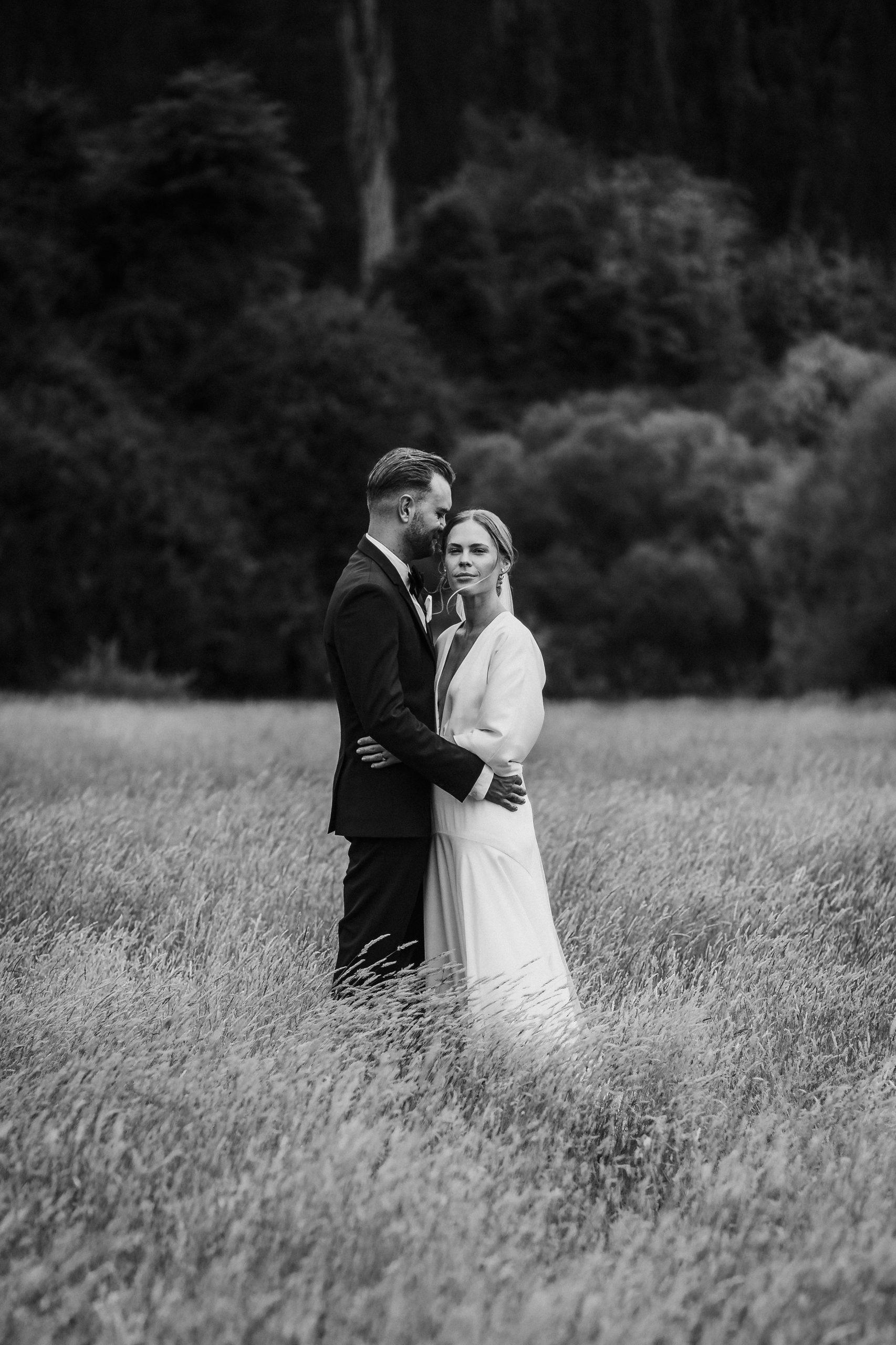 Modern Classic Bride and groom in long golden summer grass New Zealand Elopement