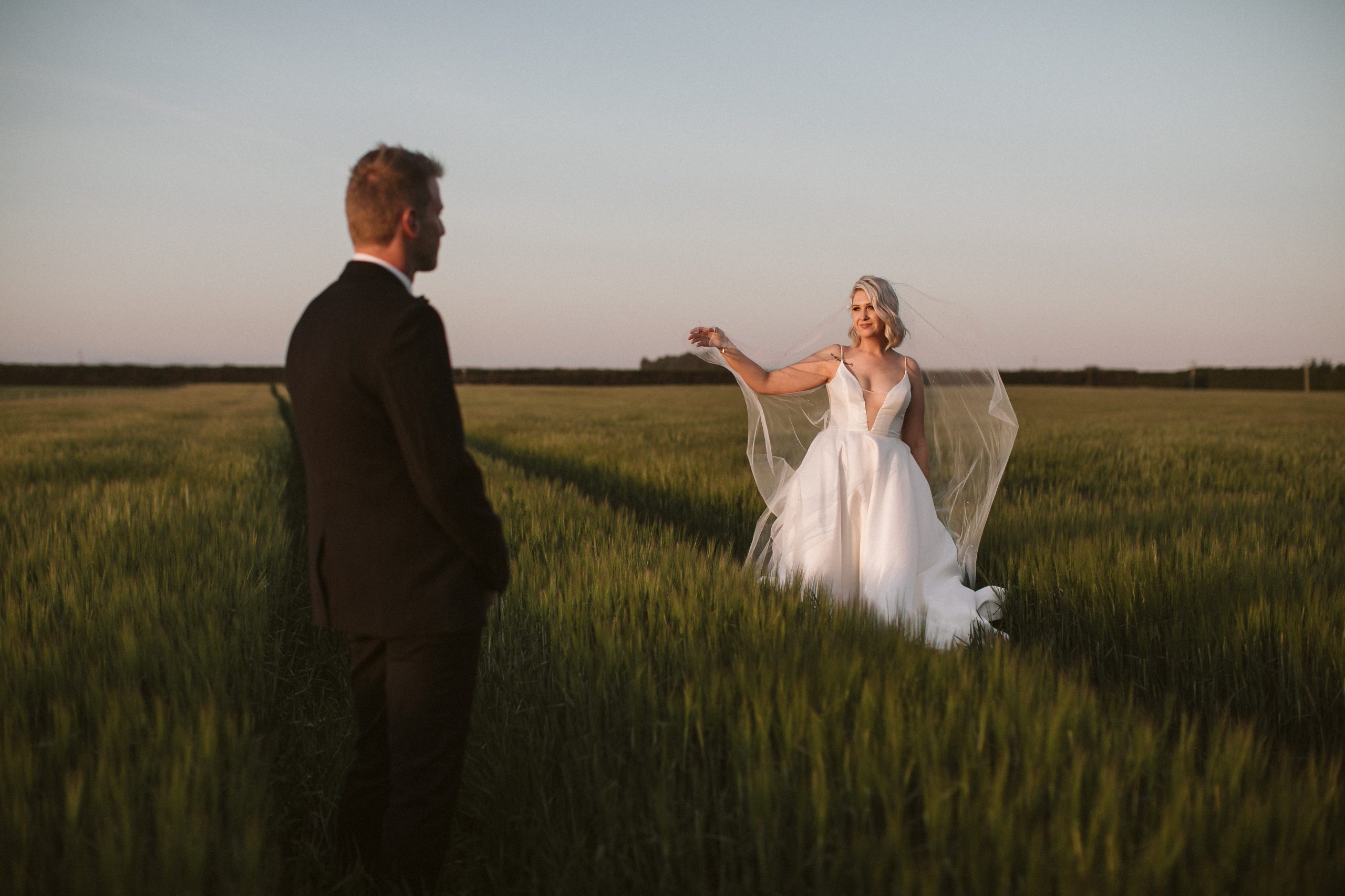 Bride and groom in wheat field at sunset