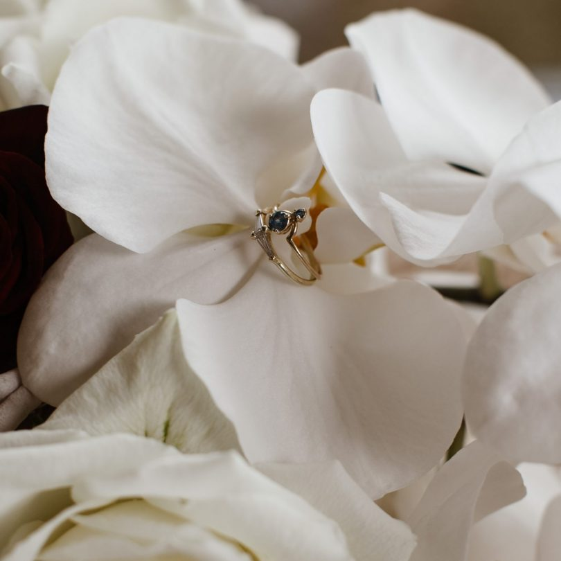 White orchid and wedding ring at modern wedding at Kauri Bay Boom rock Wedding New Zealand