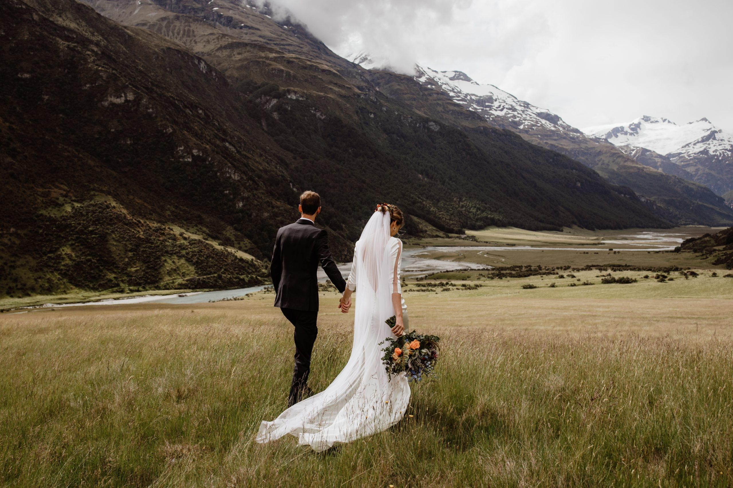 Bride and Groom during adventurous elopement looking out to the view at the top of a mountain in Queenstown New Zealand