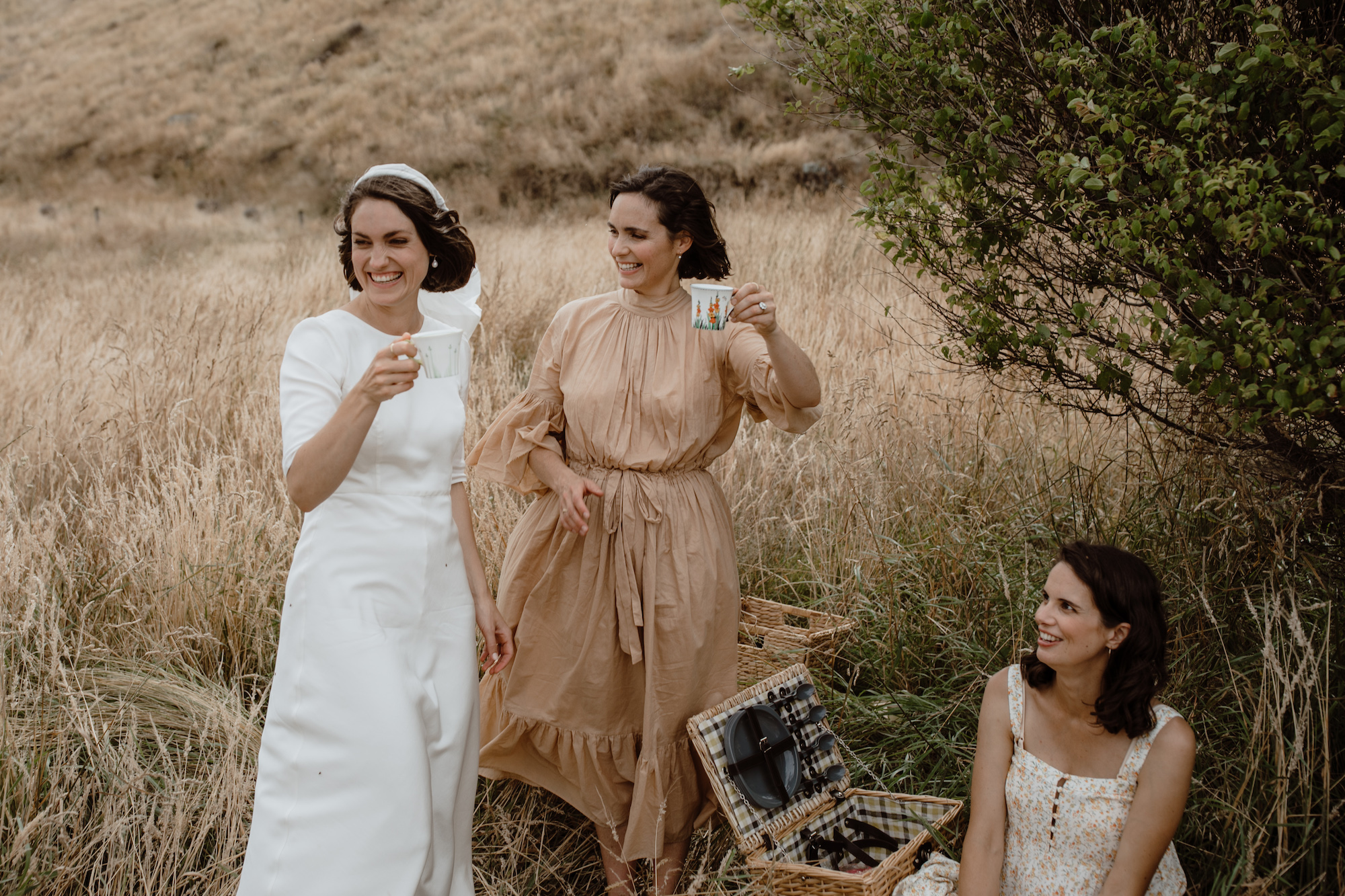 Bride and bridesmaids sharing a picnic with each other in warm tone mismatched vintage dresses amongst the soft coastal summer grass Christchurch New Zealand Ana Galloway Photography