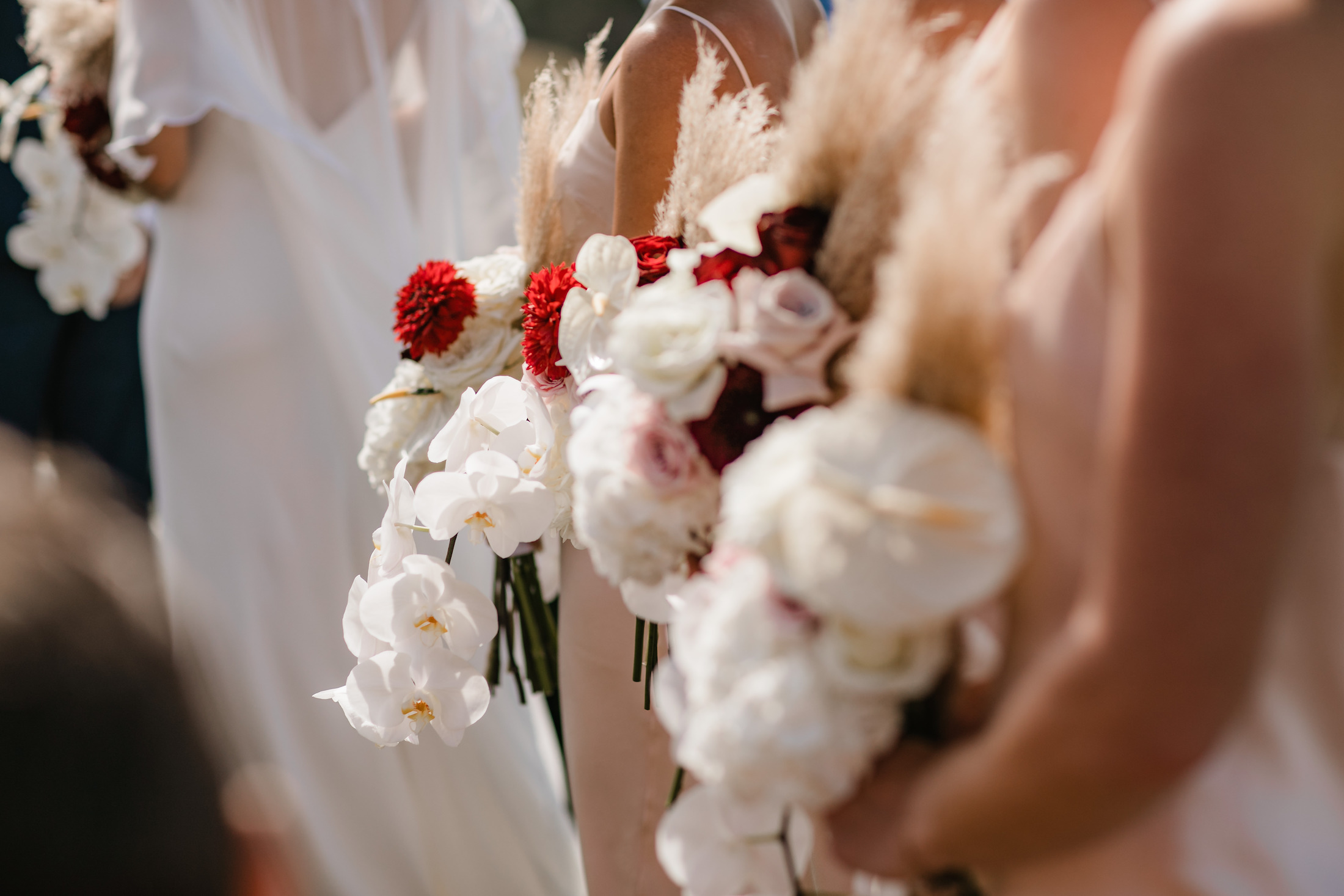 White orchid and red rose bouquets at modern wedding at Kauri Bay Boom rock Wedding New Zealand